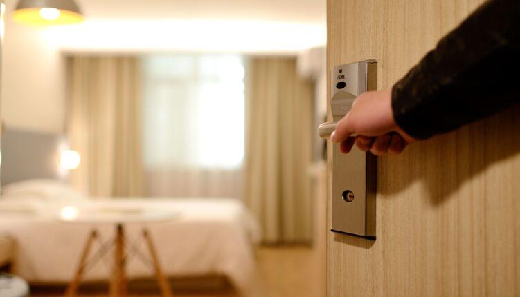 Mão abrindo porta de um apartamento.